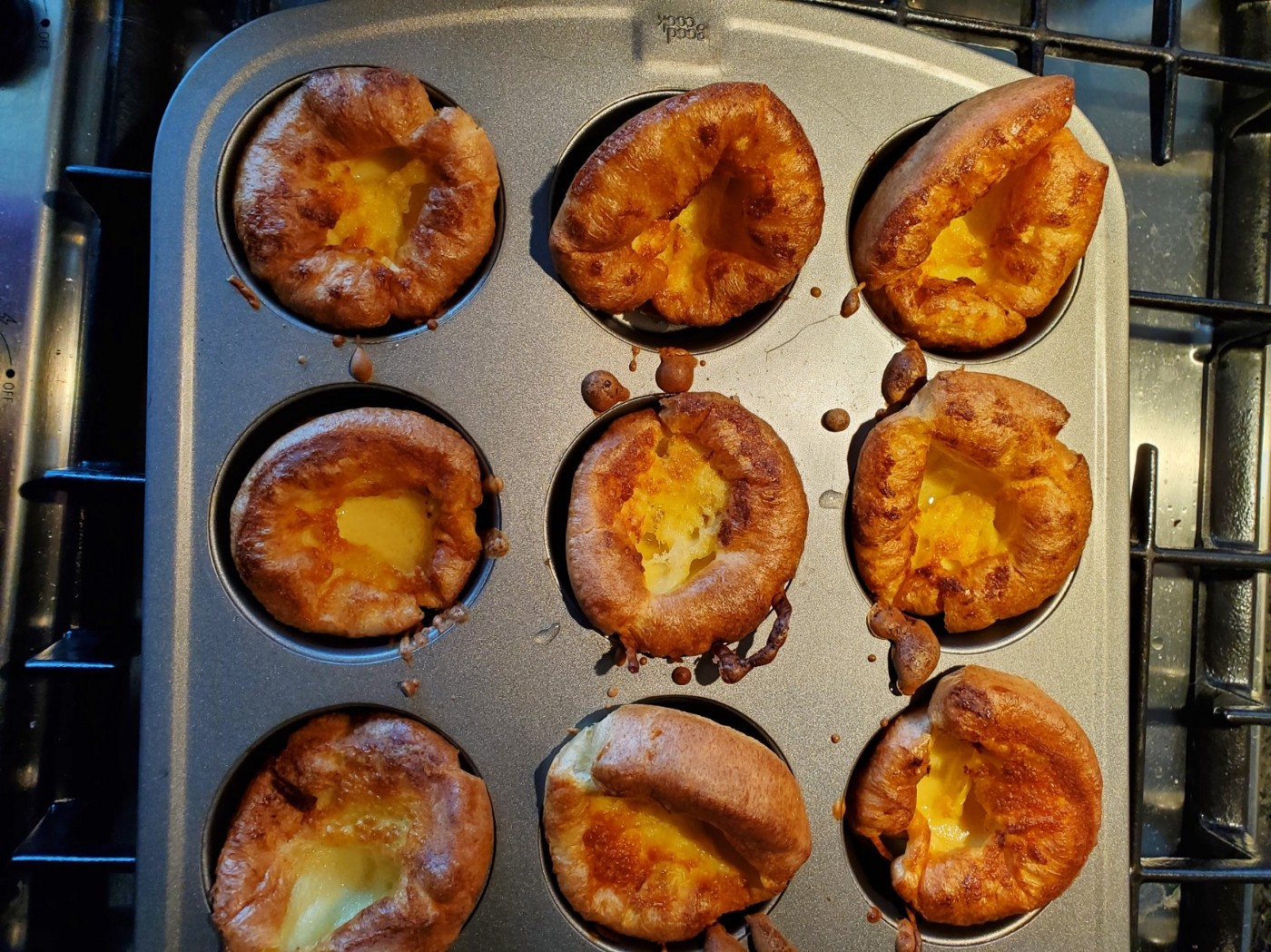 A muffin tin showing nine golden brown, cooked Yorkshire Puddings.