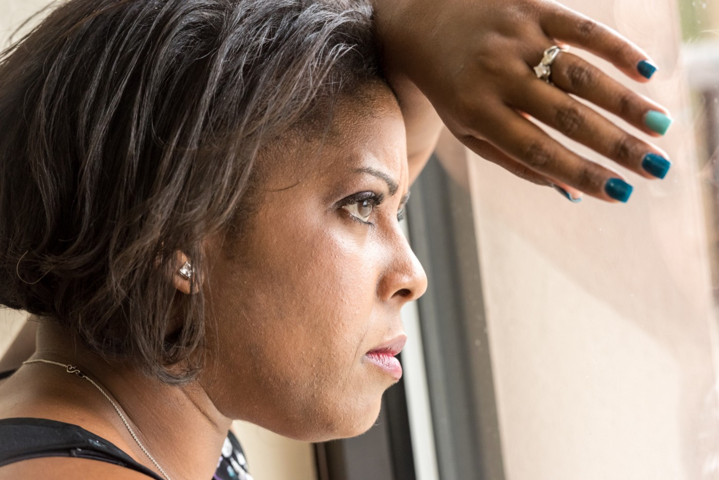 A closeup photo of a black woman leaning against a window and she looks out with a determined expression.