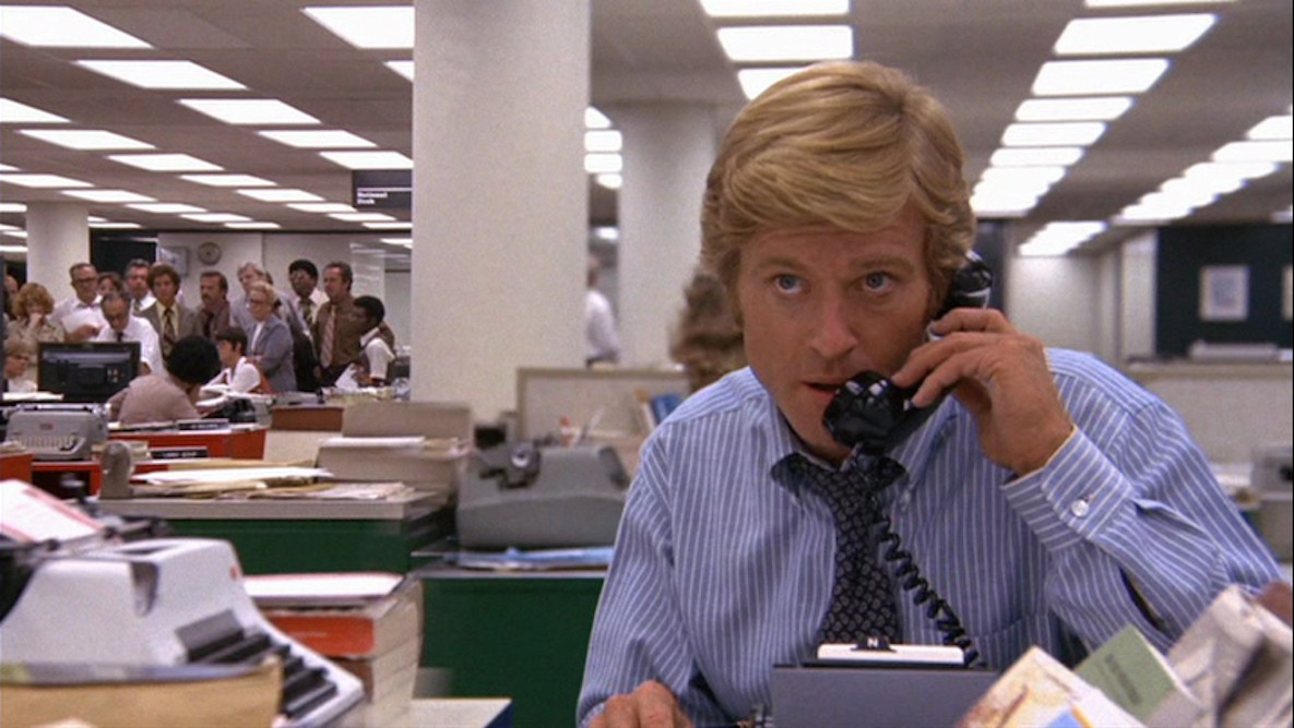 Still from the movie All the President's Men. Robert Redford is on the telephone in a newsroom.