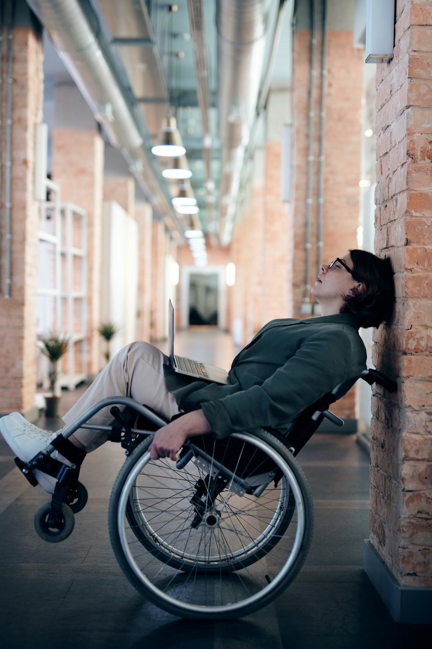 A woman in a wheelchair is leaning back against a wall in this photo