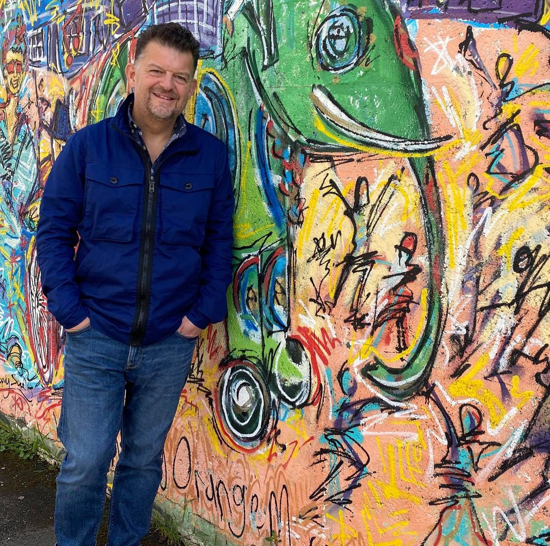 The author stood in front of a wall covered in graffiti