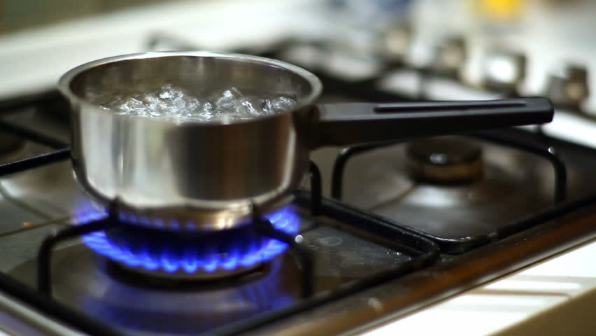 A dirty gas stove top with a small pot of water boiling on the front burner.