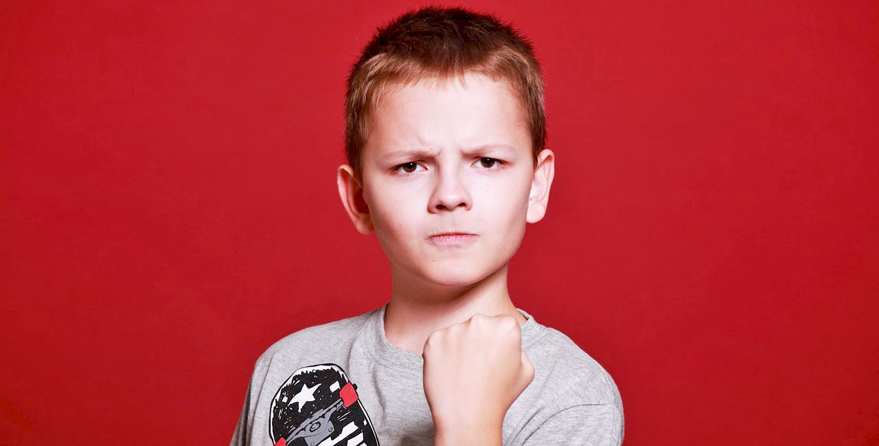 Boy with short red hair looking angrily at viewer and brandishing a fist
