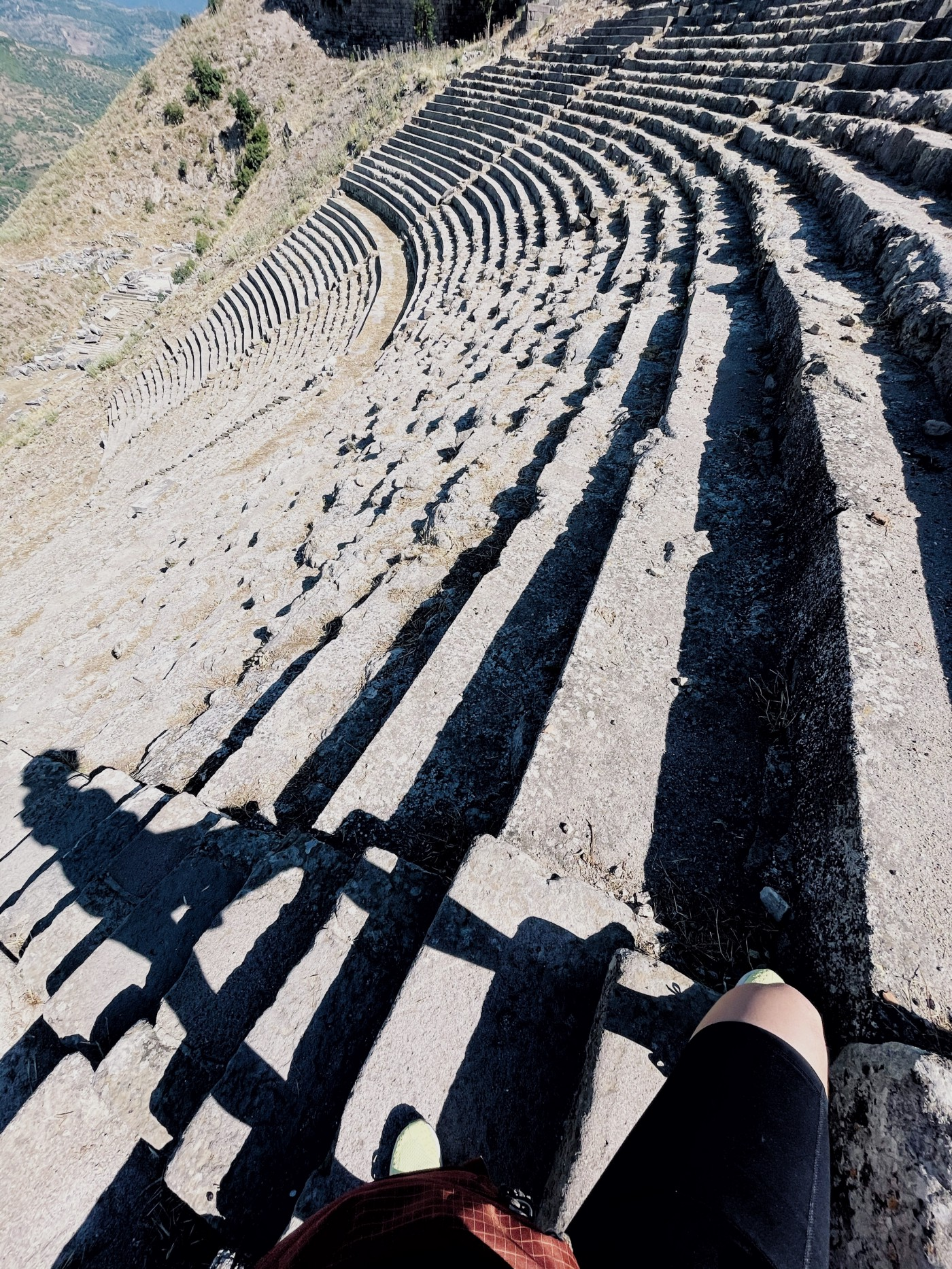 Woman's shadow over the steps of a steep antique theater in the Aegean.