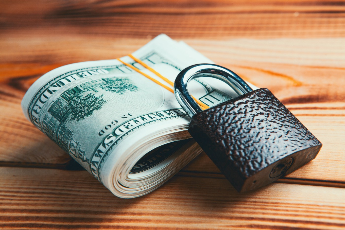 There is a large billfold of 100 dollar bills with a small rubber band around it and a lock lying ontop of and against the money.