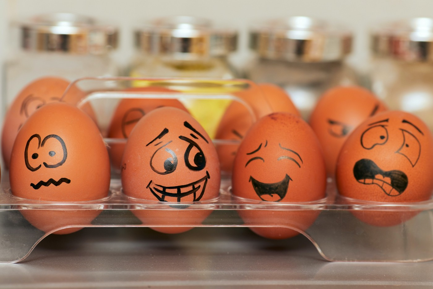 Eggs in a carton painted with faces showing different emotions.