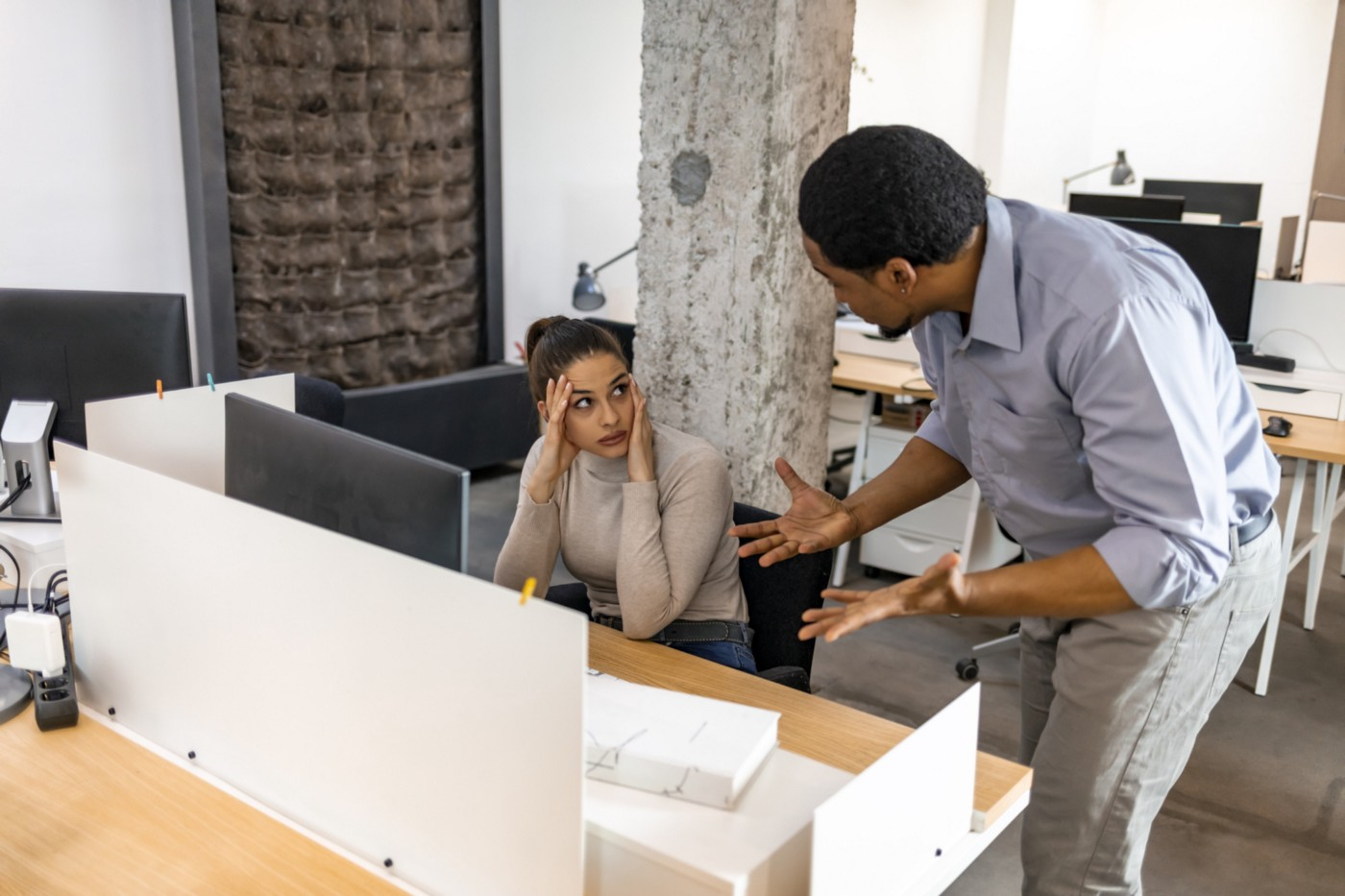 Stressed female employee with a frustrated male boss at work.