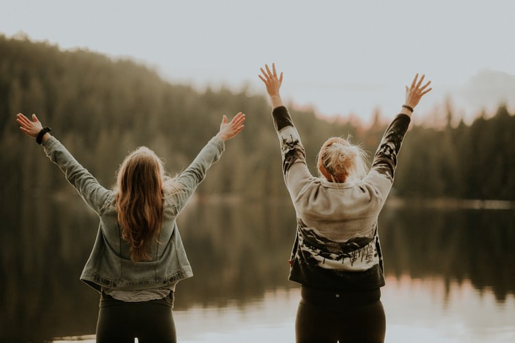 How Not to Worry Yourself Sick—two women stand facing a lake with their hands in the air