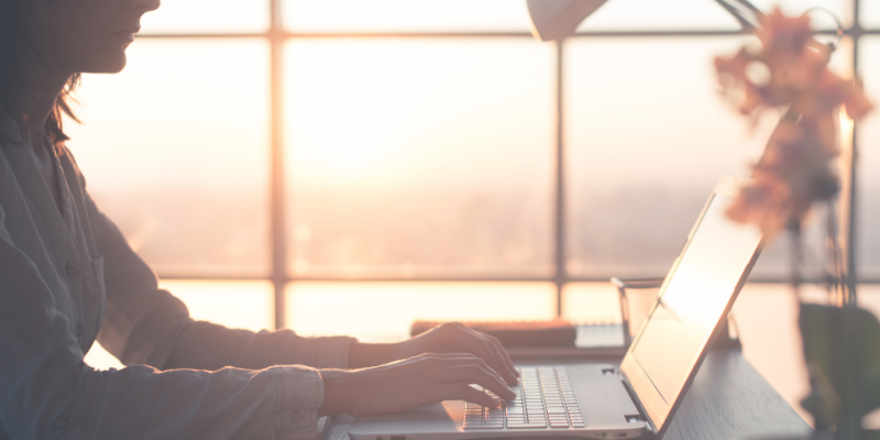 Woman typing on computer with a sunrise in the background — 5 Fresh Lessons From My First $2,000 Month as a Content Creator