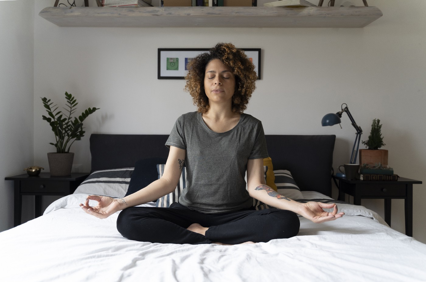 A woman sits on her bed and practices mindfulness through meditation.