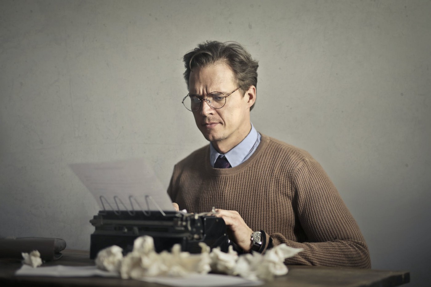 A writer writing yet looking stressed. He doesn't know how to make a living with his writing.