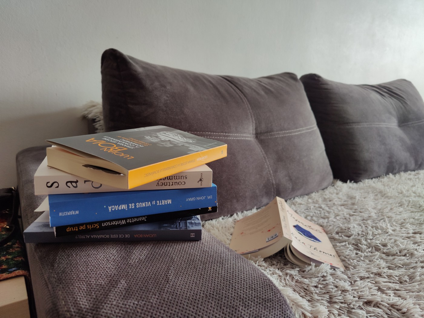 Pile of books on a sofa, with an open, upside-down book nearby
