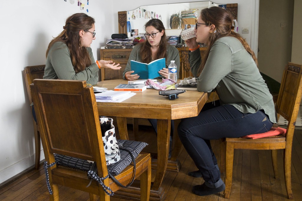 Three versions of the same woman in a green shirt sit together around a wooden table.