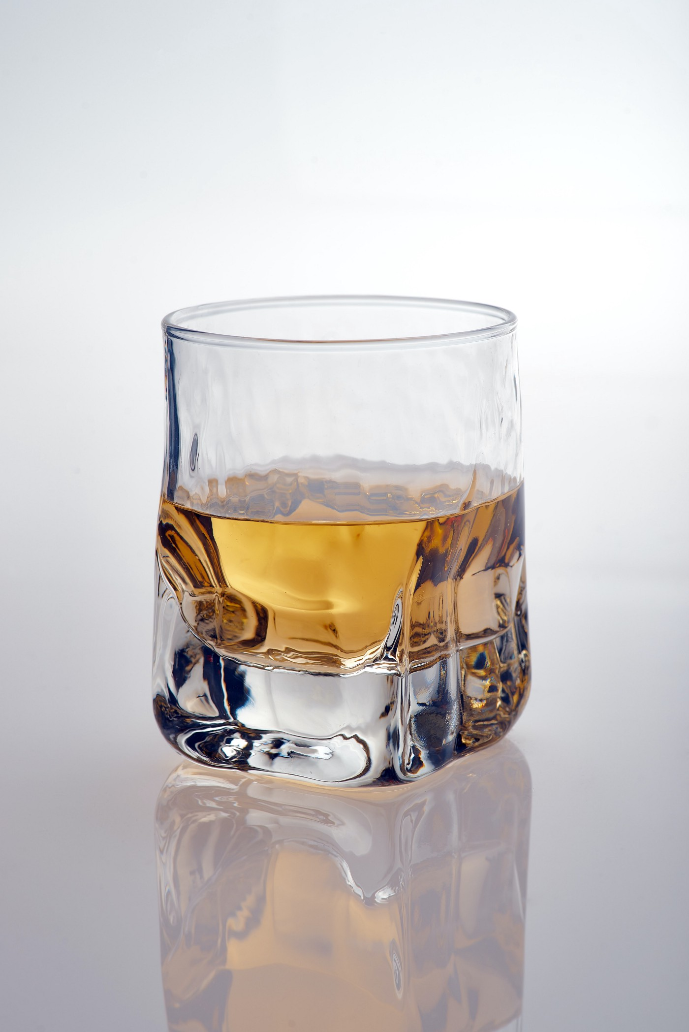 A half-filled square-shaped glass of whisky