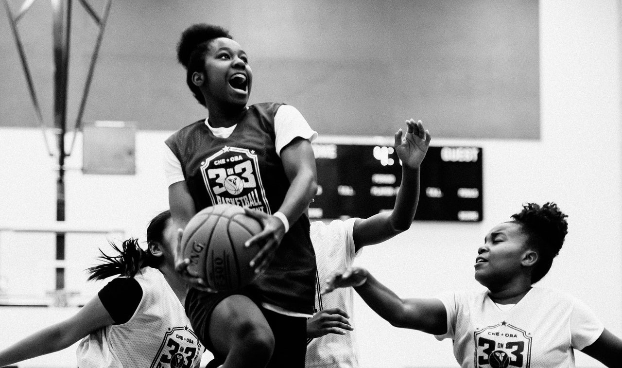 Girl basketball player going in for the dunk with an expression of joy and delight