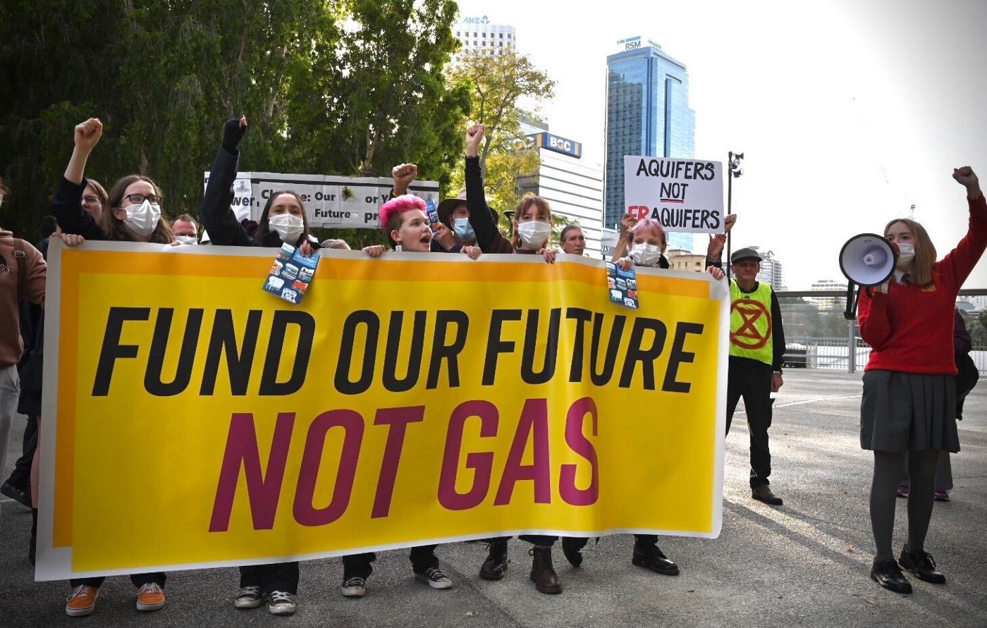 5 students holding a yellow banner that reads: Fund our future, Not gas. Also a student to right holding a megaphone.