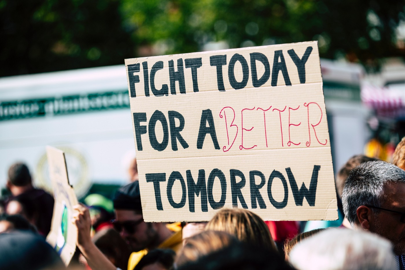 "People at a protest with a sign saying ""Fight today for a better tomorrow"""