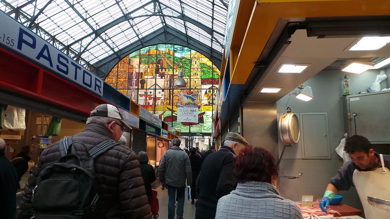 Shoppers in an indoor open-air market with a glass roof and stained-glass windows.