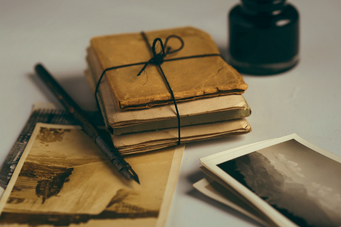 A stack of papers bound in twine with a dip pen on the left and an ink well on the right.