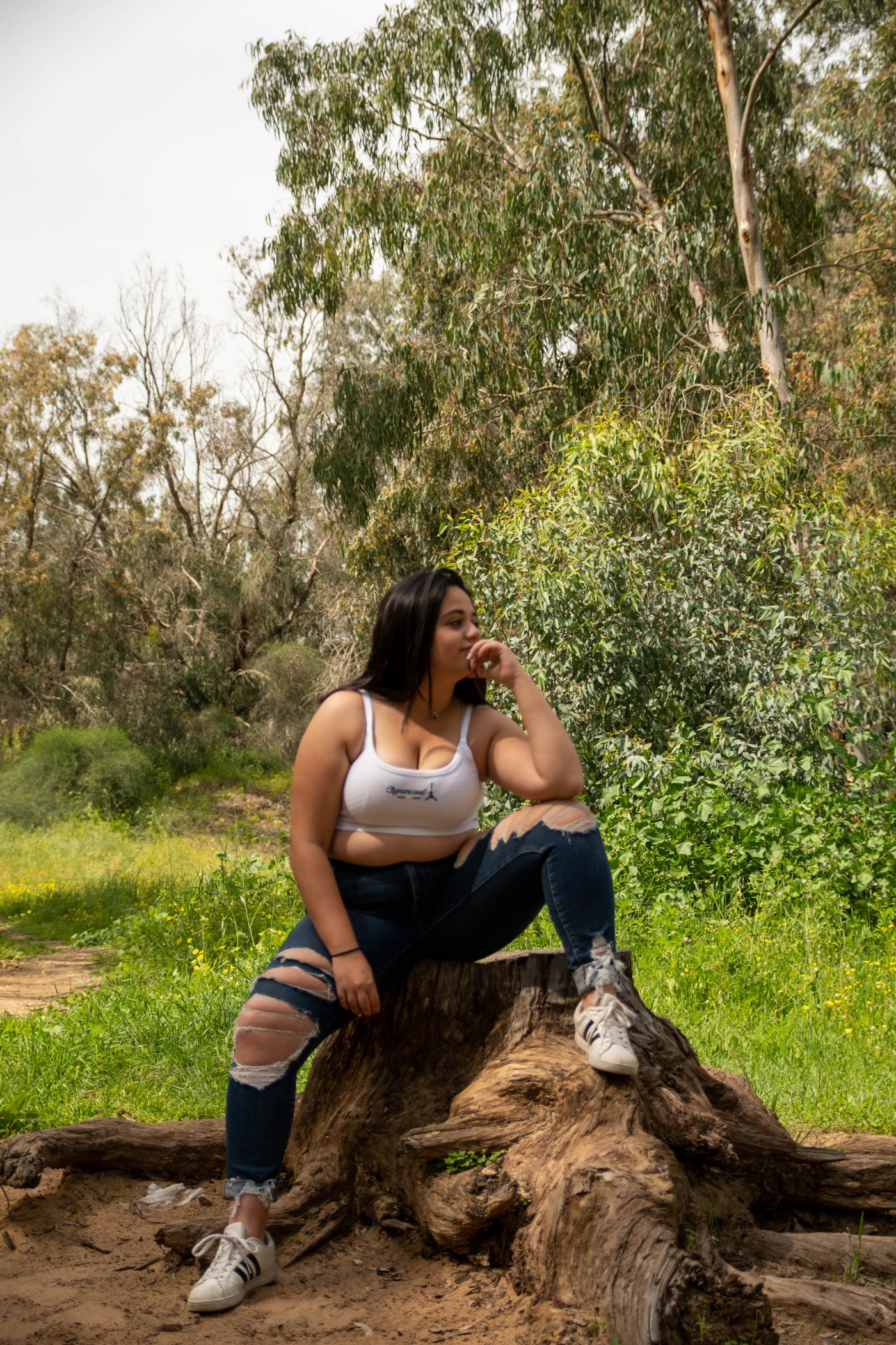 Confident plump girl wearing ripped jeans and crop top sits amongst trees.