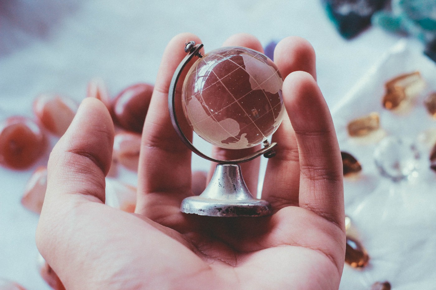 person holding globe paperweight in their hand