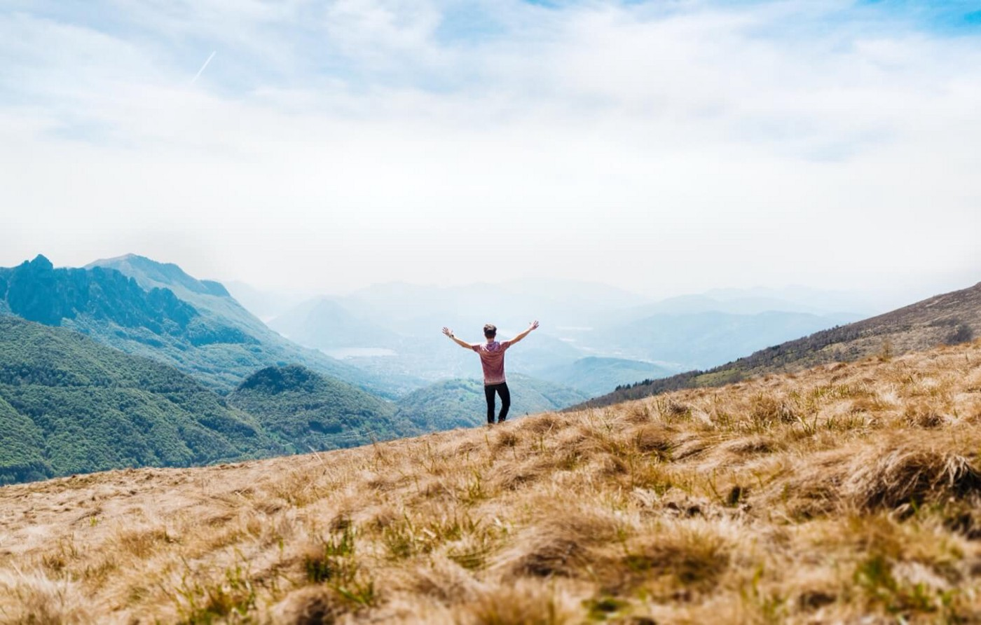 A person looking at a beautiful landscape with their arms open