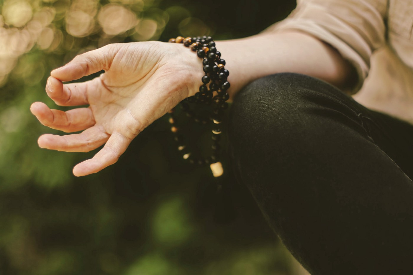 A person sitting in a meditative pose, with prayer beads strung around their wrist.
