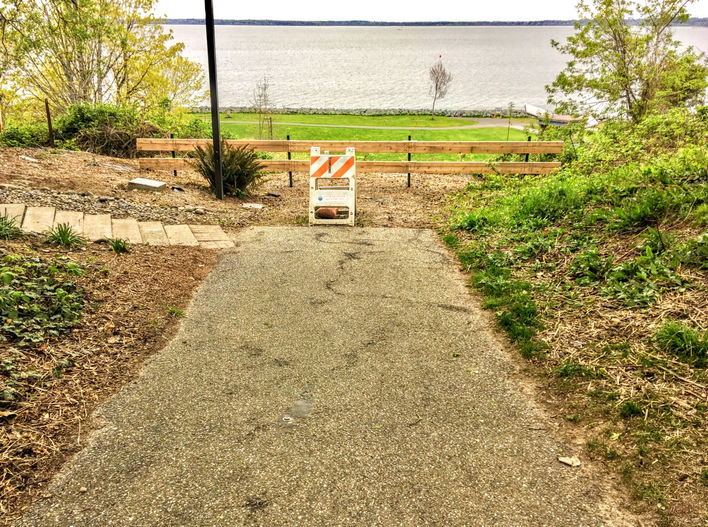 A paved trail dead-ends at a barricade with a new fence and bay in the background