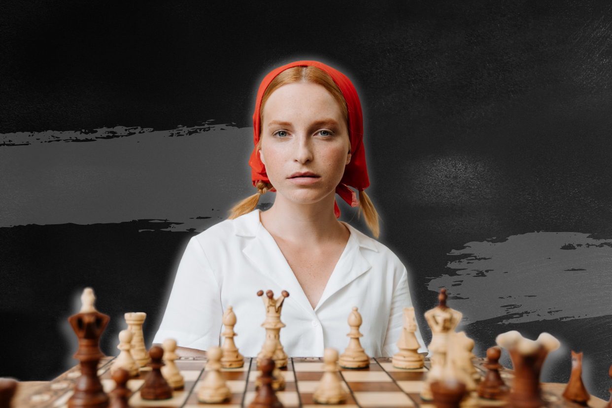 Young woman behind a chess board.