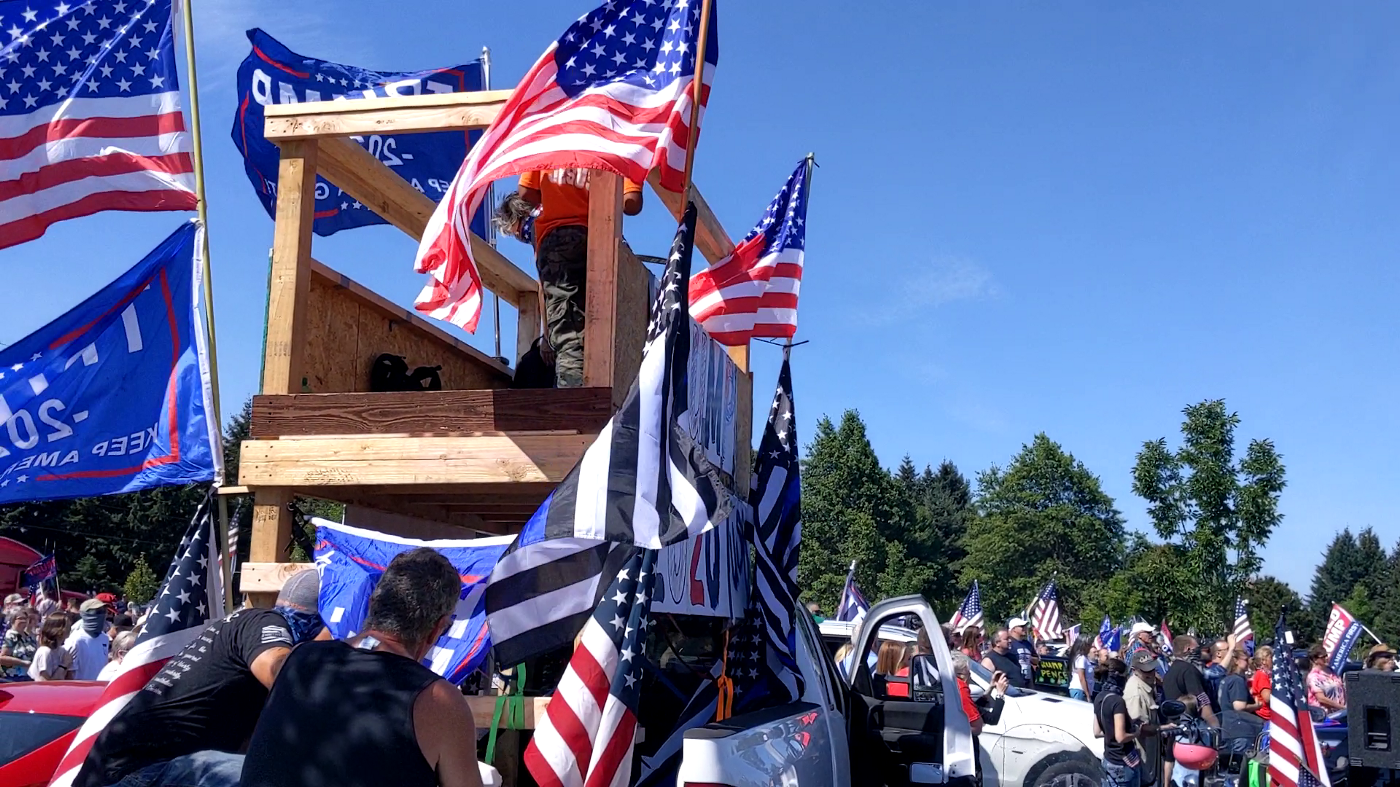 A wooden platform built onto the back of a pickup truck with several American, Blue Lives Matter, and Trump flags flying