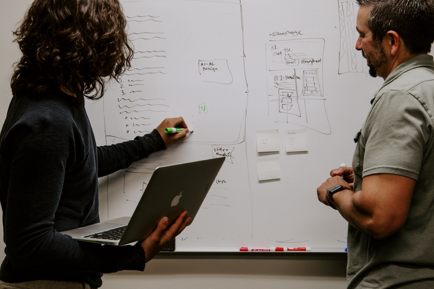 Two people working together in tandem—a woman holding a computer writing on a whiteboard and her teammate following along.