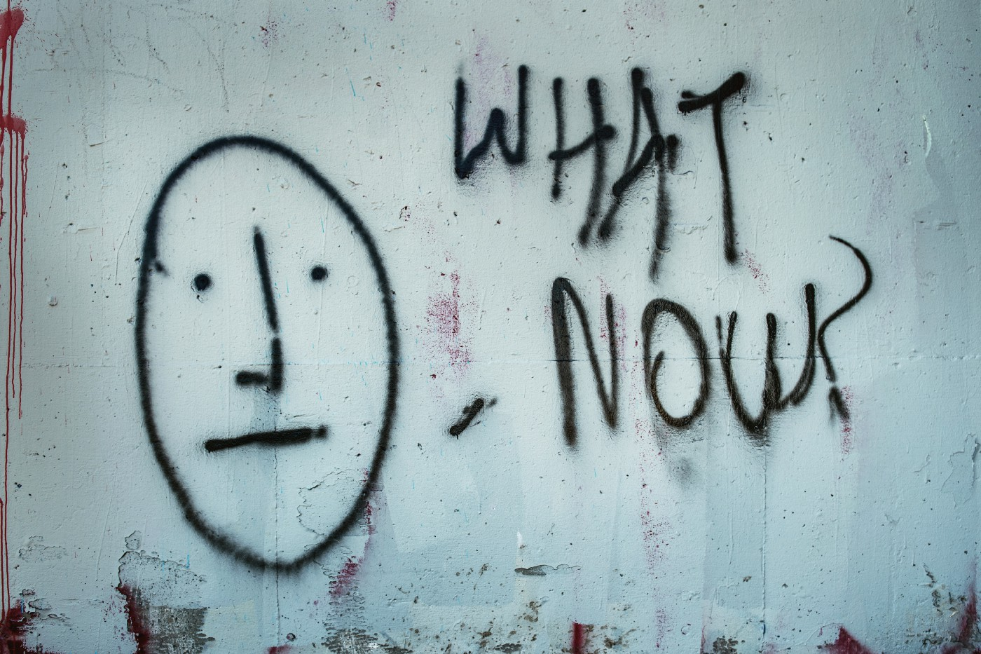 Black graffiti on a white wall—A simple, straight face with the words 'what now?'