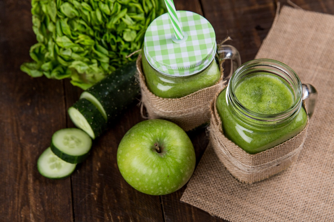 A group of objects on a kitchen table, all green. A Cucumber, apple, smoothie, and lettuce.