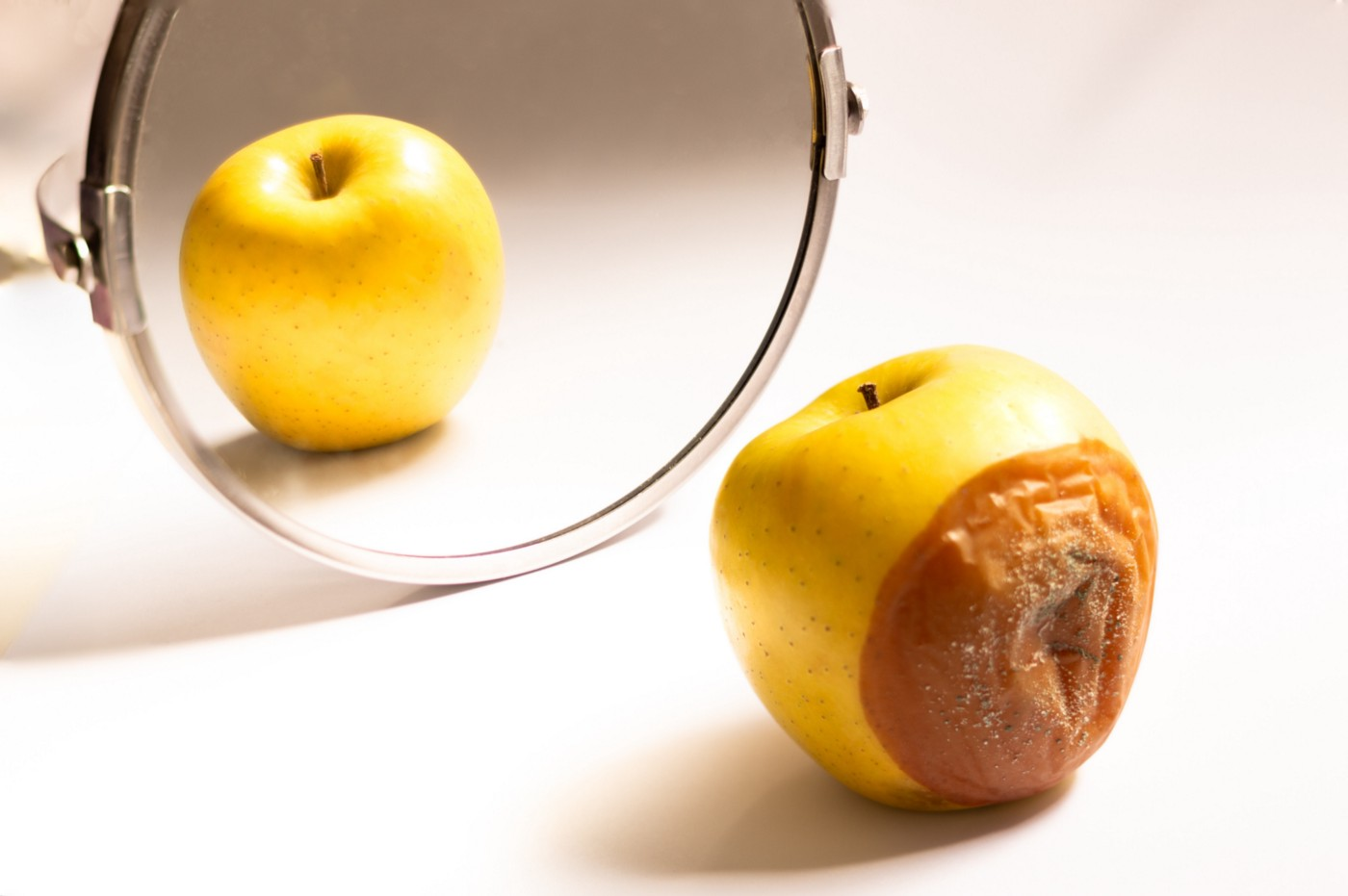 Apple that appears perfect in a mirror, because its rotten side faces away.
