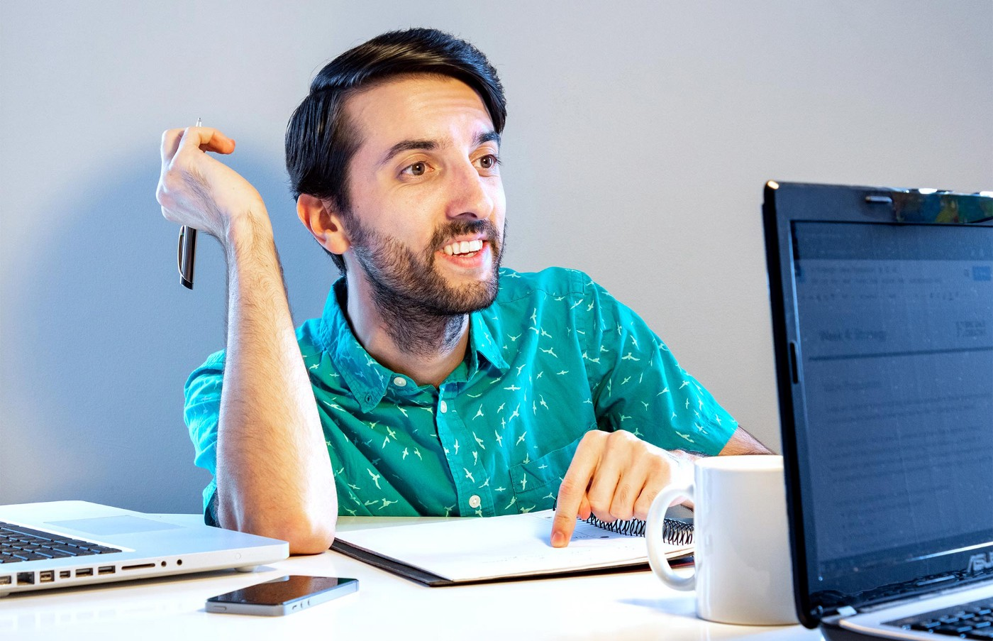 A 20-something man in a teal shirt smiles welcomingly while pointing at a notebook next to his laptop.