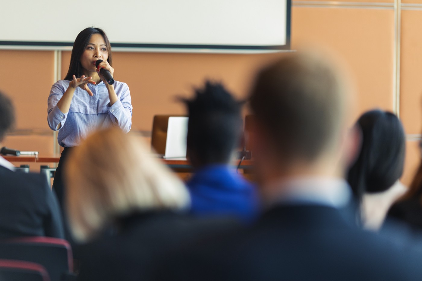 An Asian woman presenter interacting with the audience at a business presentation in the board room.