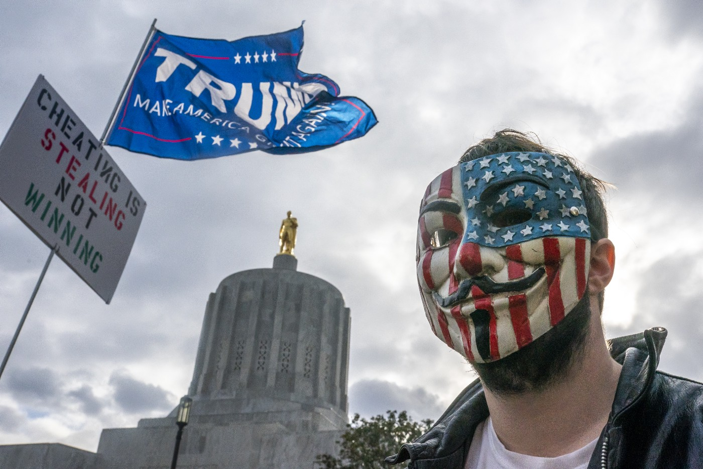 A protester in a Guy Fawkes mask stands in front of the Oregon State Capitol building during a Stop the Steal rally on Nov. 7