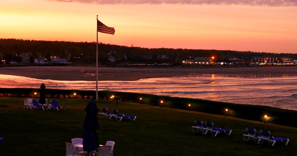 American flag on pole flies at sunset near body of water and picnic table and chairs.