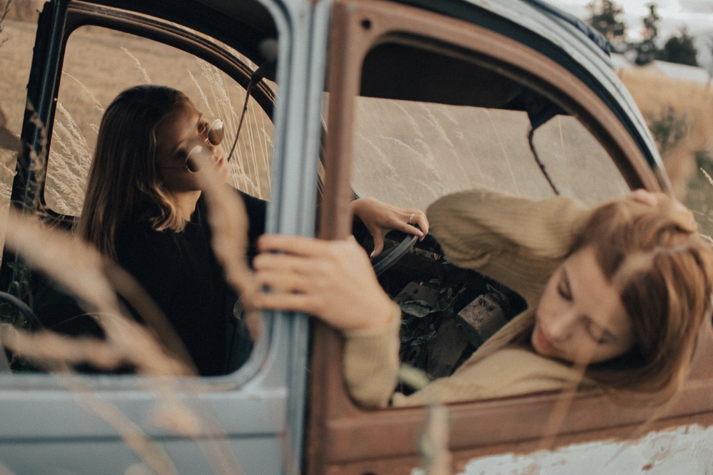 Two girls looking sad in an old car.