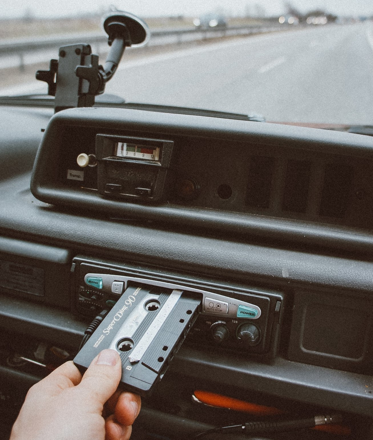 Hand placing a cassette into the car player