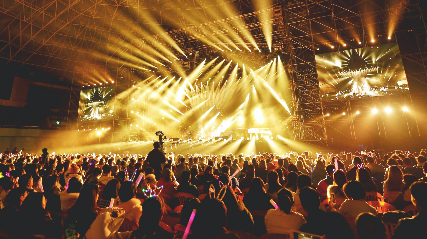 A large stage with huge adjacent screens stream large yellow lights into the large energetic crowd below