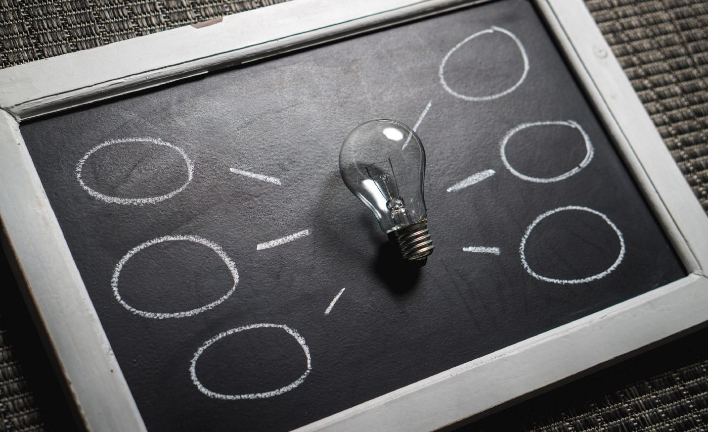 A lightbulb sits on a chalkboard with several smaller circles drawn to the right and left to represent new ideas.