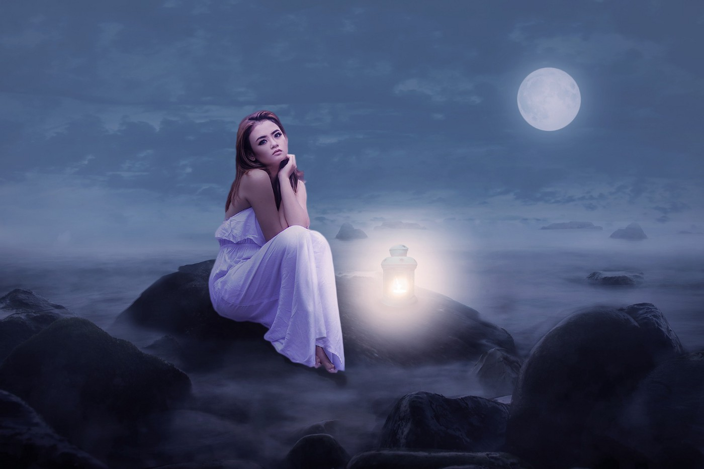 Woman in white gown sitting on the rock under the moonlight