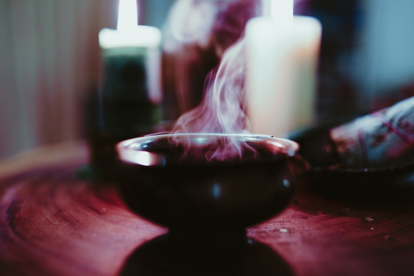 Smoke coming out of a cauldron in front of candles.
