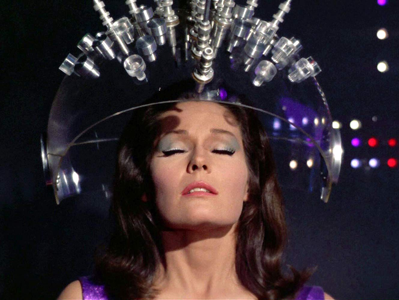"""A still from """"Spock's Brain,"""" an episode of Star Trek. The image contains a woman wearing a futuristic helmet."""