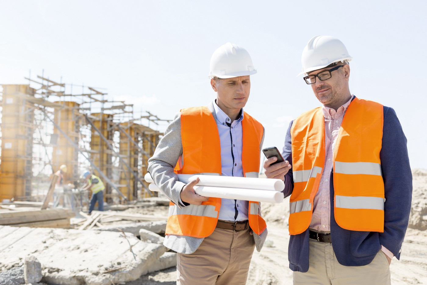 Two male engineers look at a mobile phone to see the Maturix platform at a construction site under a clear, sunny sky.