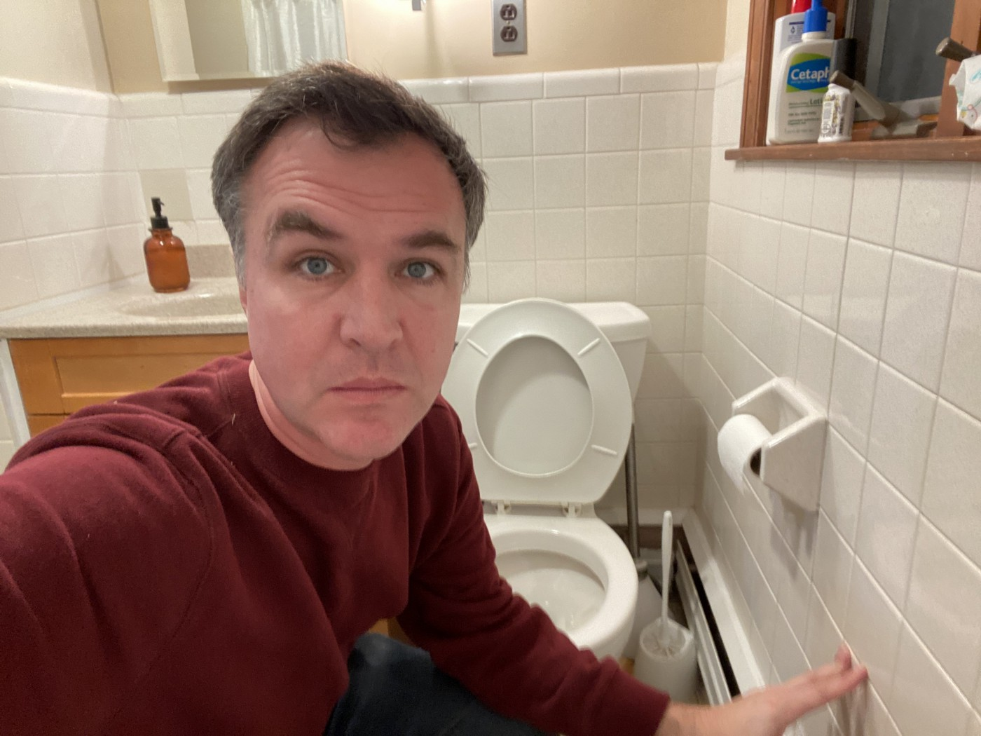 Matt Farley, a TikTok creator, poses for a selfie next to a toilet in his restroom.
