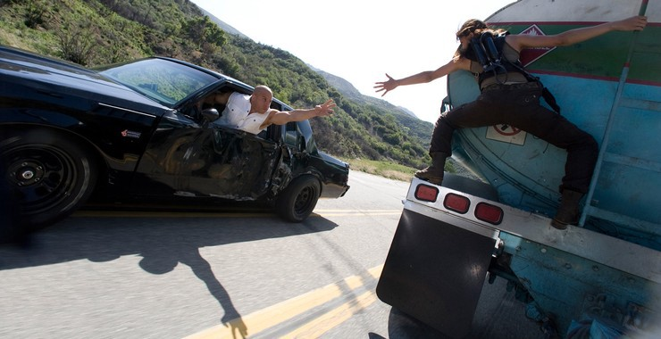 A still from the film Fast and Furious in which Vin Diesel reaches for Michelle Rodriguez as the two travel on separate vehicles