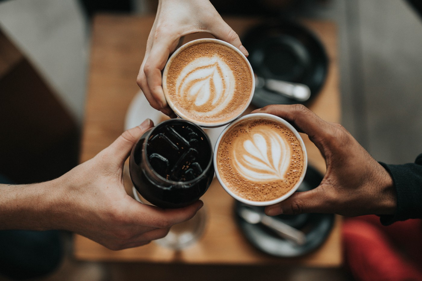 Three people toasting with three cups of coffee
