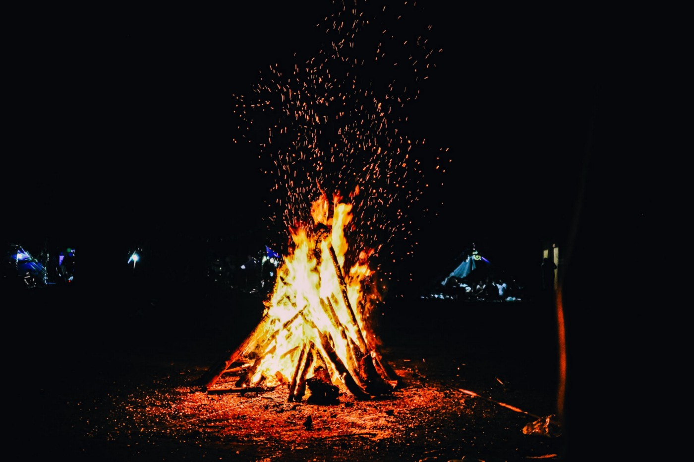 A bonfire sparks against a dark sky